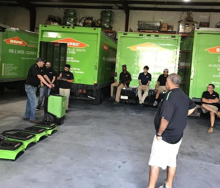 SERVPRO employees sitting around a garage on vehicles looking at equipment.