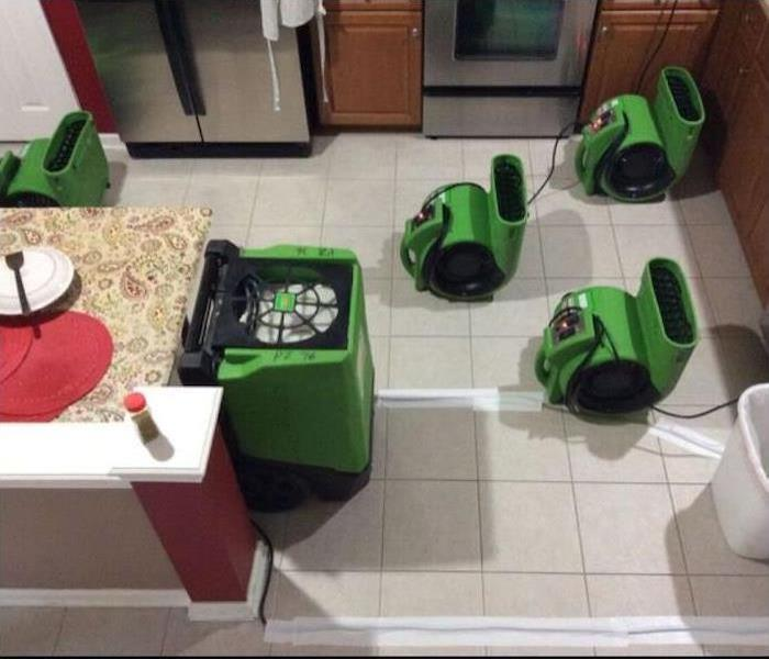 Air movers and dehumidifiers sitting in the floor of this kitchen