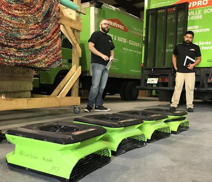 Two SERVPRO trucks in a garage with two men looking at equipment.