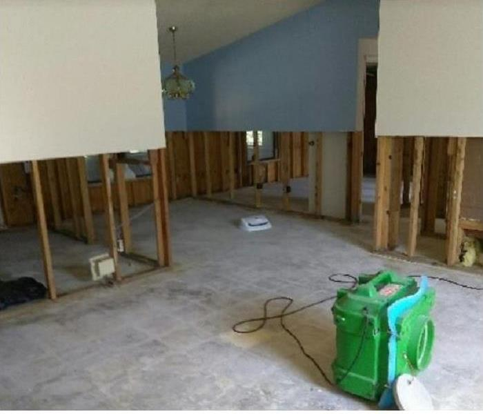 SERVPRO drying equipment in water damaged room; flood cuts on walls to enable drying